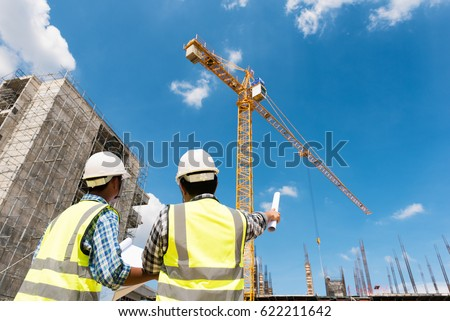 Construction engineers discussion with architects at construction site or building site of highrise building