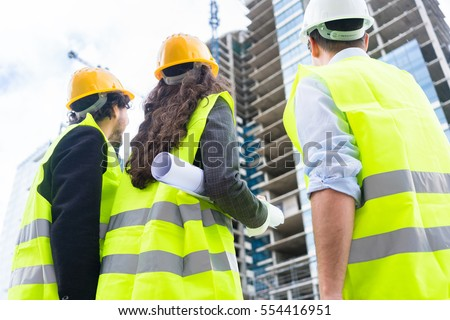 Construction engineers or architects at building site of highrise building #554416951