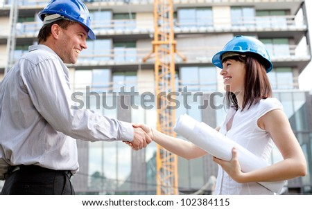Construction engineers shaking hands at the construction site. Selective focus.