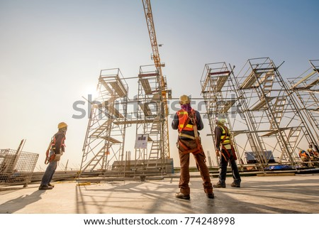 Construction engineers supervising progress of construction project stand on new concrete floor top roof and crane background #774248998