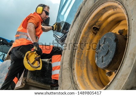 Construction Equipment Operator. Caucasian Industrial Worker in His 30s and Heavy Duty Machinery.