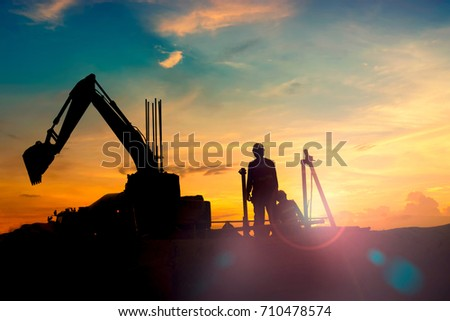construction equipment's silhouette on sunset ,Loader truck and mobile crane is coming up hill in the foggy morning in back country during construction road and infrastructure.Petroleum industry
