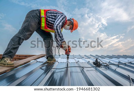 Construction expertise worker with face mask wear safety uniform install new roof, Roofing tools, Electric drill used on new roofs with Metal Sheet. worker roofer builder working on roof structure.