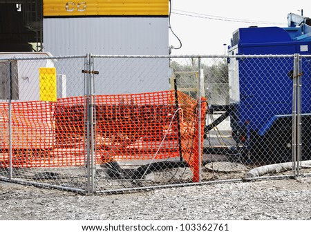 Construction fences and storage units in bright primary colors and rectangular shapes create abstract design.