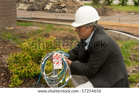 construction foreman attaching a lockout tag to electrical wires