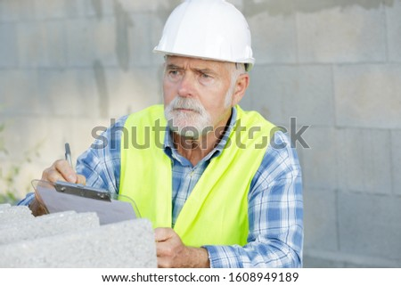 construction foreman builder on building site clipboard
