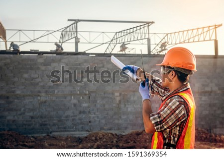 construction foreman talking on walkie-talkie holding.