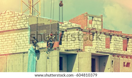 Construction. Group of builders in hard hats with plastering tools plaster a wall in a site. Industrial climbers hanging on a rope, plaster a house.Vintage on old paper background for your text