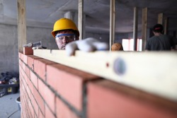 Construction guy helmet measures level brickwork. Level is used when laying bricks in order to check verticality. High quality and stable reading. Indoor use equipment. Smooth brickwork