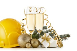Construction hard hat, fir tree branches, two glasses with champange and Christmas ornament isolated on a white background. New Year and Christmas. Horizontal view