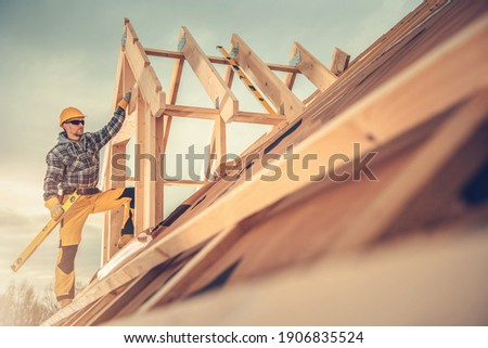 Construction Industry Theme. Caucasian Contractor Worker in His 40s with Sprit Level Tool in His Hand on the Roof of Newly Built Wooden House Roof Structure. Сток-фото ©