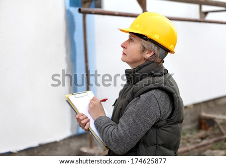 Construction inspector examine styrofoam insulation of house facade, wall