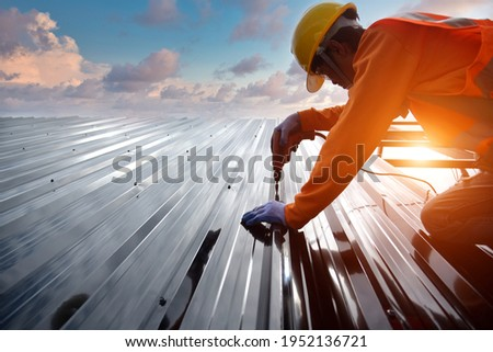 Construction install new roof,Roofing tools,Electric drill used on roofs with Metal Sheet Roofer working on roof structure of building on construction site,Roofer and Metal Sheet on top roof.