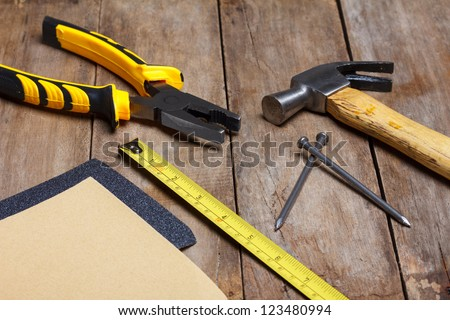 Construction instruments on wooden table - sandpaper, pliers, measuring tape, hammer, nails