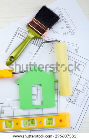 Construction instruments, plan and brushes over house plan on wooden table background