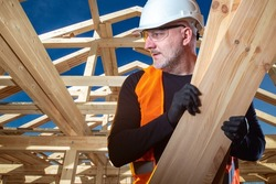 Construction loader worker. Worker carries two wooden beams. Loader on background of house under construction. Concept - man is engaged in unloading lumber. Builder at work. Erection wooden cottage.