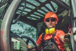 Construction Machine Operator. Caucasian Worker Inside Modern Industrial Machinery.