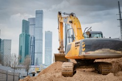 construction machinery and excavator on the background of skyscrapers. concept of building buildings, bridges and roads
