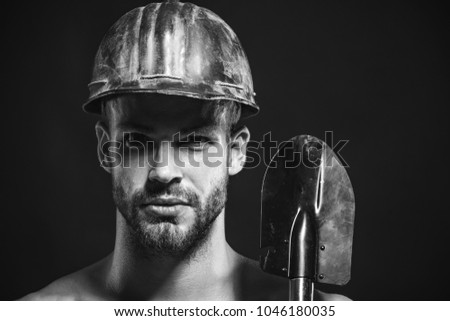 Construction male worker portrait holds sapper shovel. Labour, occupation, engineer, industry man, repairman, builder or miner wears protective helmet holds shovel. Closeup. Copy space. Black & white.