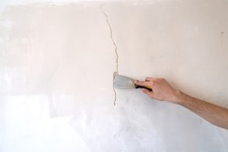 Construction man worker repairing a crack wall of a home, plastering cement on wall. Builder applying white cement to a crack in a wall with a putty knife. close up