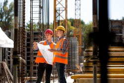 Construction manager and engineer dressed in orange work vests and hard helmets explore construction documentation on the building site near the steel frames