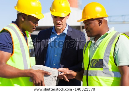 construction manager and two workers examining a brick