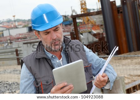 Construction manager controlling building site with plan - stock photo