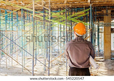 Construction manager with blueprints standing in front of construction site. #545220547
