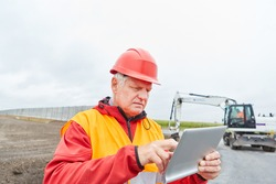 Construction manager with tablet computer on the construction site of the road construction in the new development area