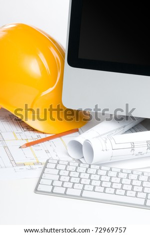 Construction manager workplace with blueprints, computer, protective helmet and pencil
