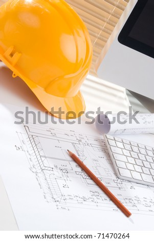 Construction manager workplace with blueprints, protective helmet, computer and pencil