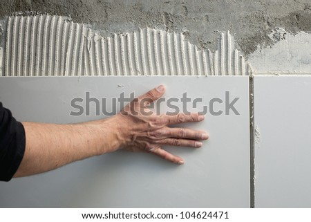 construction mason man hands on tiles work with notched trowel cement mortar