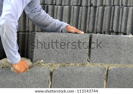 construction mason worker bricklayer installing  brick with trowel putty knife outdoors