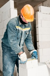 construction mason worker bricklayer measuring a brick with measure tape