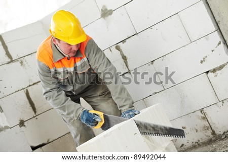 construction mason worker bricklayer sawing off a calcium silicate lime sand brick