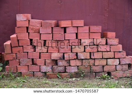 Construction Materials. Building materials for construction of residential complex. Pile of red bricks at construction site.