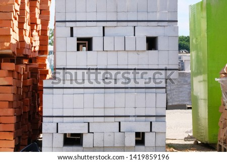 Construction Materials. Building materials for construction of residential complex. Pile of white bricks at construction site.