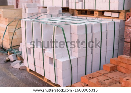 Construction Materials. Building materials for construction of residential complex. Pile of white bricks at construction site