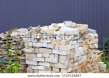Construction Materials. Building materials for construction of residential house. Pile of brickwork at construction site. Bricks stacked.