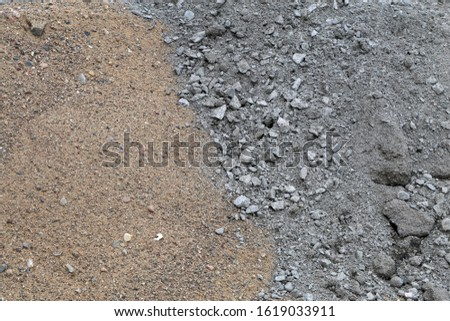 Construction materials in a construction site. In this photo you can see brown sand and grey crushed grey stone material. Closeup color image with beautiful textures.