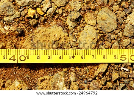 construction meter with centimeters on earth background