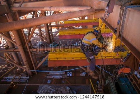 Construction miner abseiler worker wearing safety harness, face shield setting on the mono rail beam fall arrest position,  performing metal surface grinding preparation mine site,Perth Australia