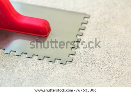 Construction notched trowel is a tool for tiles installation work