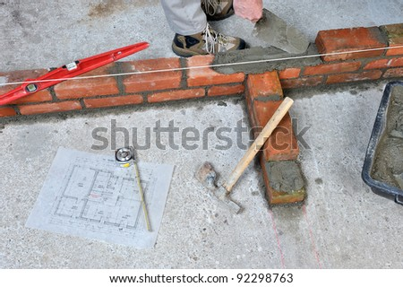 construction of a brick wall by a bricklayer