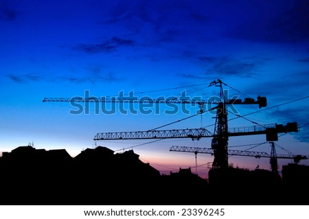 Construction of a building, cranes and other machinery as silhouettes against a background of red sunset sky