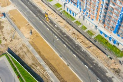 Construction of a city street, laying of communications, installation of sewer hatches, gutters, curbs improvement of the street, after laying asphalt. Preparation for paving, aerial view