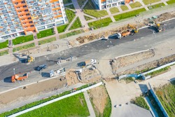 Construction of a city street, laying of communications, installation of sewer hatches, gutters, curbs improvement street, after laying asphalt. Preparation for paving, aerial view