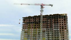 Construction of a high-rise building. Monolithic technology. Construction crane, bricks. Workers install ventilated facade and warm exterior walls. Tilt-shift effect. Blurred.