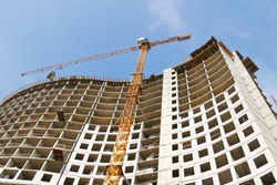 Construction of a multi-storey hotel complex. Construction site background. Crane and building under construction. Construction of a multi-storey hotel complex.