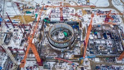 Construction of a new nuclear power plant in the city of Kurchatov. Kursk NPP-2. Two round-shaped power units. People and equipment are on the construction site.